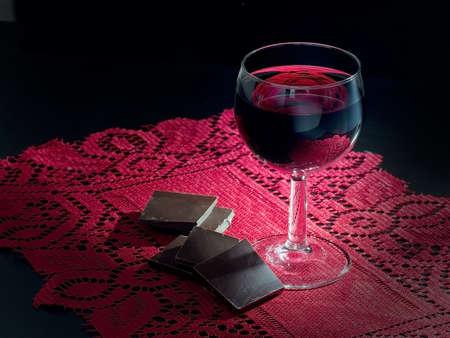 El vino tinto y chocolate negro. Estilo claroscuro. El encaje rojo. Foto de archivo - 49036354