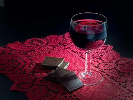 Red wine and dark chocolate. Chiaroscuro style. On red lace. Standard-Bild