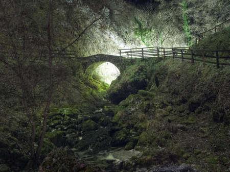 Magical night scene. Mystical old bridge in fog.