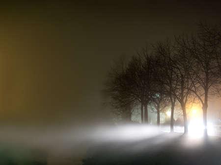Foggy night scene. Passing traffic creates extra light. Stock Photo