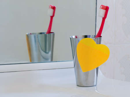 differential focus: Toothbrush and mug with heart note. Differential focus.