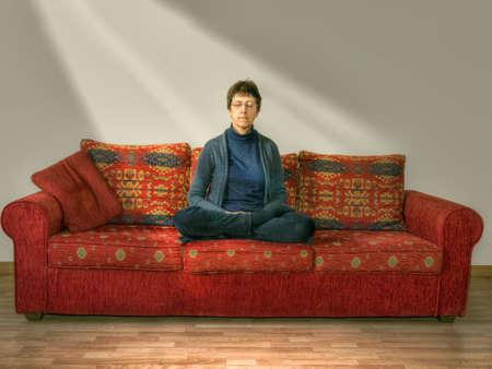 Wellness. Middle agec woman on sofa. Lotus position with light. Фото со стока