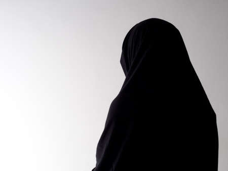 oppression: Woman in chador from behind, with copyspace