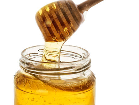 golden pot: Honey pot with wooden drizzler, isolated on white, close.