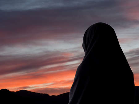 spiritual woman: Evening prayers, Muslim woman in chador aganst sunset sky. Stock Photo