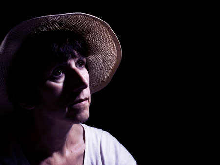 wistful: Middle aged woman in straw hat, wistful. Filtered, colored image.