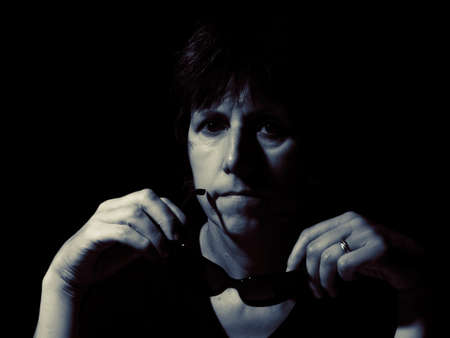 impassive: Portrait of a middle aged woman, with sunglasses. Pensive. Toned image.