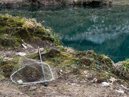 gone: Empty net, lake behind. Gone fishing, no catch.