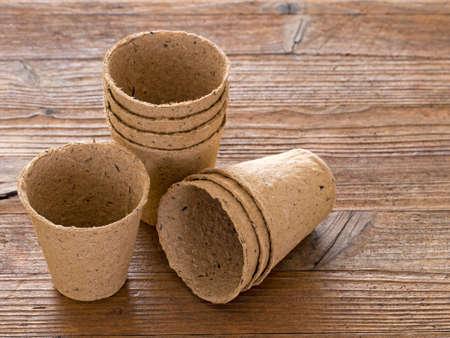 turba: macetas de turba para jardinería primavera. El banco de madera. Foto de archivo