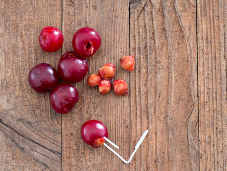 Sour cherries with paperclip to remove stones. On rustic wooden board.