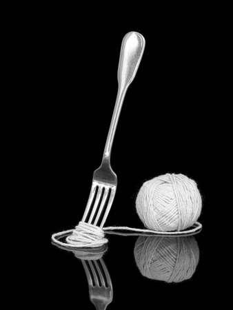 Monochrome black and white. Fork and spaghetti string.
