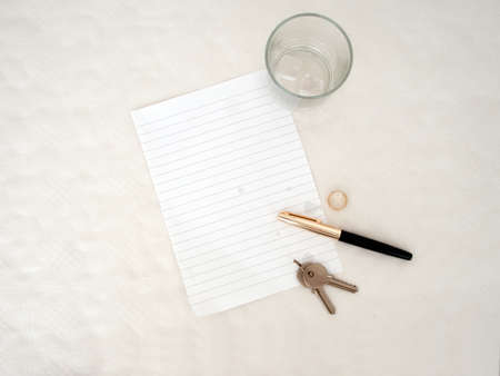 Marriage breakup, blank for your message. Objects include pen, keys and wedding ring on tear stained paper.