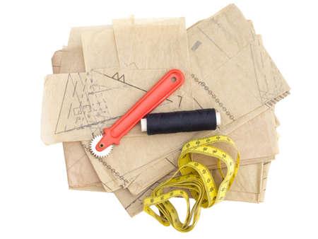 Confección, equipo de costura aislado en blanco. Hilo de patrón de papel, marcador, etc.