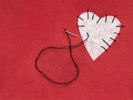 Fabric heart red with white patch and black sewing thread. Mend broken heart concept.