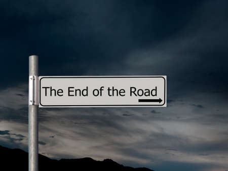 The end of the road, sign over dark, gloomhy cloud sky background. Concept, politics,, Brexit etc.