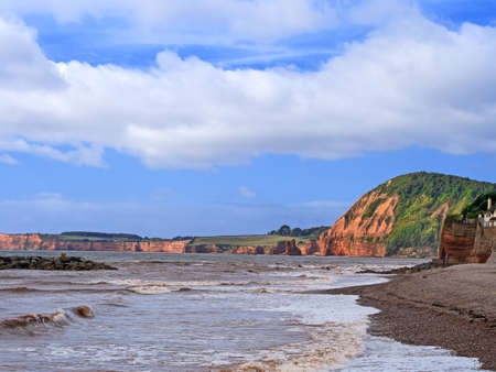 Sidmouth Beach, Devon, England. View towards Ladram Bay, red cliffs in late summer sun. On the Jurassic Coast. Stock Photo