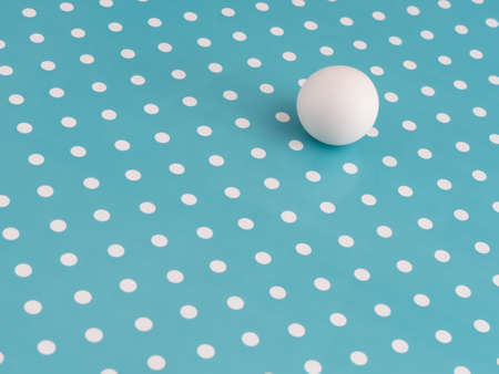 Large white marble ball amongst small dots on turquoise. Different, unique or just trying to adapt, fit in. Hiding in plain sight, concept.