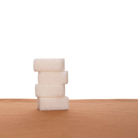 Stack of four sugar cubes on fabric, white background. Healthy eating.