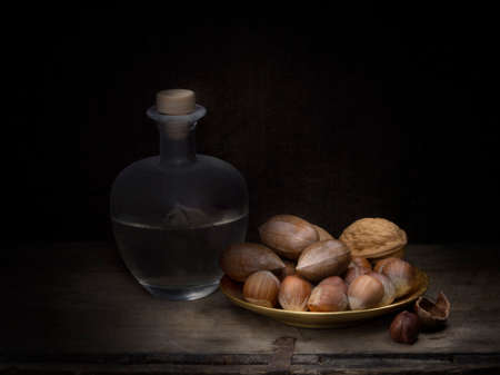 Rustic home made grappa with asorted nuts, still life light painting.