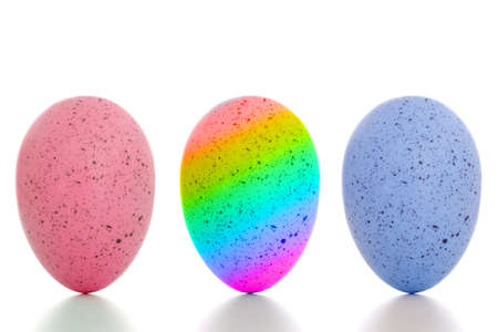 Blue, pink and rainbow painted eggs, standing upright, on white background with shadow. Gender studies etc.