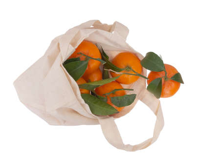 Fresh picked oranges in reusable, recyclable fabric shopping tote bag, isolated on white. For environmentally friendly, green consumers.
