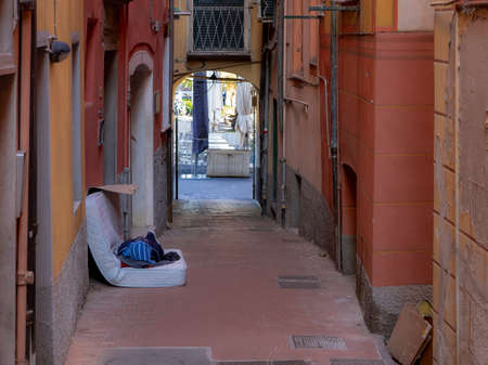 Homelessness. Unidentifiable man sleeps on old mattress in the street, Italy - Lerici. 스톡 콘텐츠