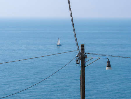 A small yacht sailing away from modern life and technology ie the cables and land. Freedom, escape concept, metaphor.