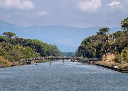Ancient wooden bridge over river in scenic Natural Park of Migliarino San Rossore Massaciuccoli. Near Pisa, in Tuscany, Italy. Stock Photo