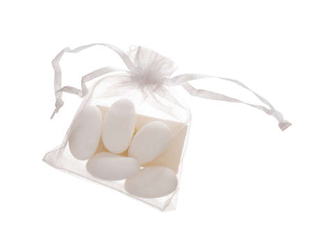 Bomboniere contents, 5 sugared almonds in bag with note, traditionally given as wedding favour, gift in Italy and called confetti. Isolated on white.
