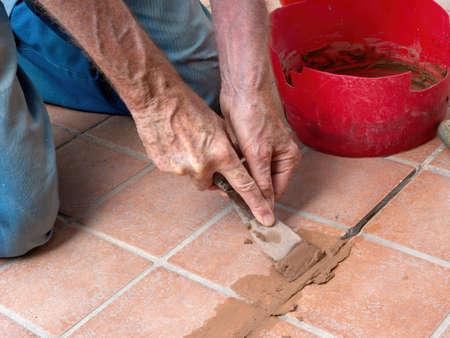 Unidentified man, workman, repairing grout between outdoor terracotta style patio tiles. Stock Photo