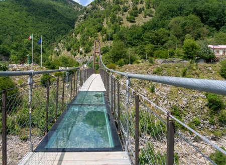 Il pannello di vetro trasparente al centro del ponte pedonale sospeso sul lago di Vagli vicino al villaggio di Vagli di Sotto, Italia. Archivio Fotografico