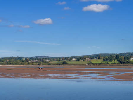 Sunny day view of the river Exe estuary at Exmouth, with unidentifiable boat grounded on sandbank. Devon, England. Low tide.
