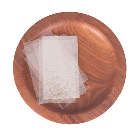 Sheets of colourless gelatin aka gelatine leaves on a wooden plate isolated on white. Food ingredient.