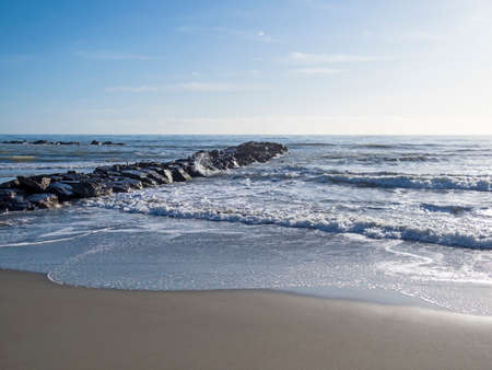 Sandy beach with breaking waves and rocky jetty. Mediterranean Sea, Europe.