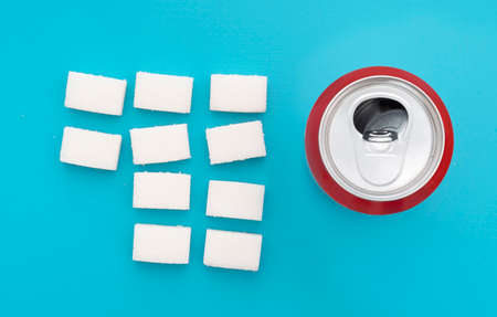Unhealthy food concept - sugar in carbonated drinks. Sugar cubes and fizzy cola drink can. Flat lay, overhead view.