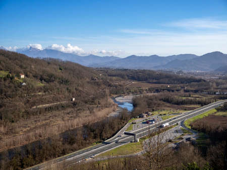 Lunigiana, north Tuscany, Italy. View from Lusuolo over motorway towards Apennine mountains. Unidentifiable vehicles etc. Sunny spring day, 2020.