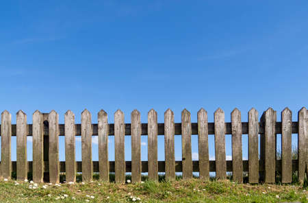 Wooden picket fence with grass, daisies and blue summer sky behind. Unpainted, natural wood. Imagens