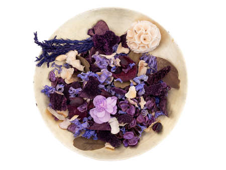 Potpourri in an old gold colour bowl, isolated on white. Purple, mauve shades.