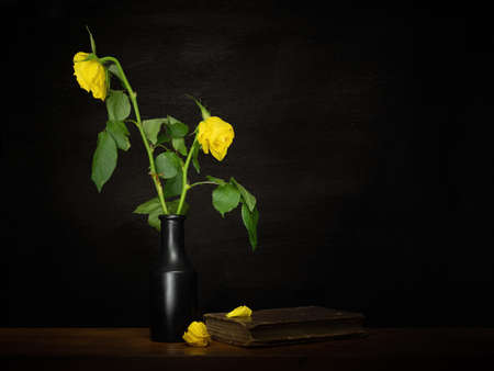Dead yellow roses in a vase with book and fallen petals. Life, death, loss concept, metaphor.
