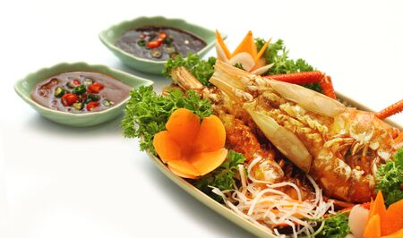 Thai style golden river prawn with garlic and pepper, served with exotic sauce on green plate and white background Stock Photo - 10732819