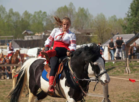 adroitness: a girl in the national Ukrainian suit executes a trick on a horse