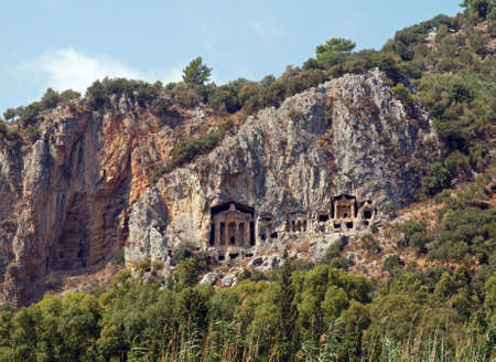 Tombs of the ancient Lycia rulers in rocks on the riverside Dalyan in Turkey photo