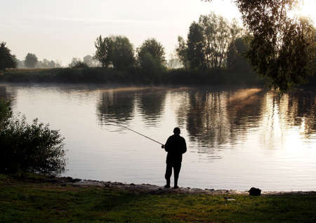 Fisherman catches fish with a fishing rod in the early morning Banque d'images