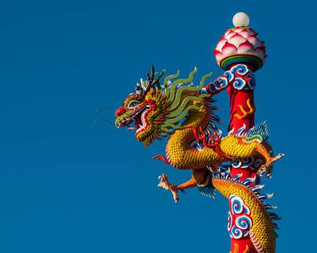 minutiae: Dragon statue on pillar and blue background  Stock Photo