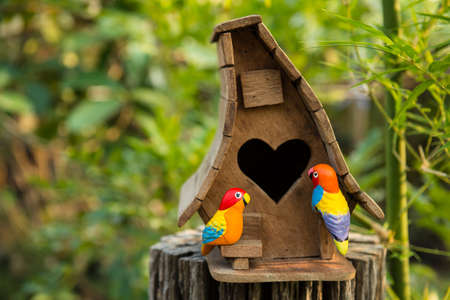 Birdhouse have a heart-shaped entrance and two lovebird made of a stucco  photo