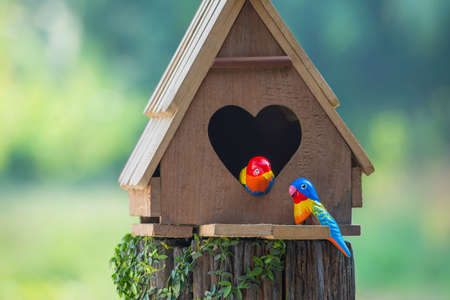 Birdhouse have a heart-shaped entrance and two love bird made of stucco