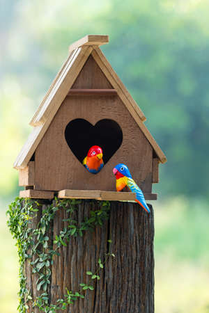 two minds: Birdhouse have a heart-shaped entrance and two love bird made from stucco Stock Photo