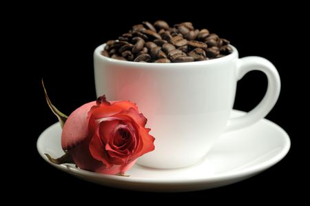 cup full of coffee beans and a rose  photo