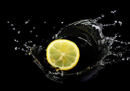 Splashing lemon into water isolated on black background