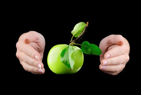 Hands and green apple isolated on black